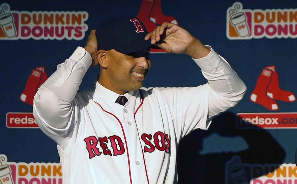 Alex Cora adjusts his baseball cap as he is introduced as the Boston Red Sox baseball teams new manager during a news conference in Boston, Monday, Nov. 6, 2017. (AP Photo/Michael Dwyer)