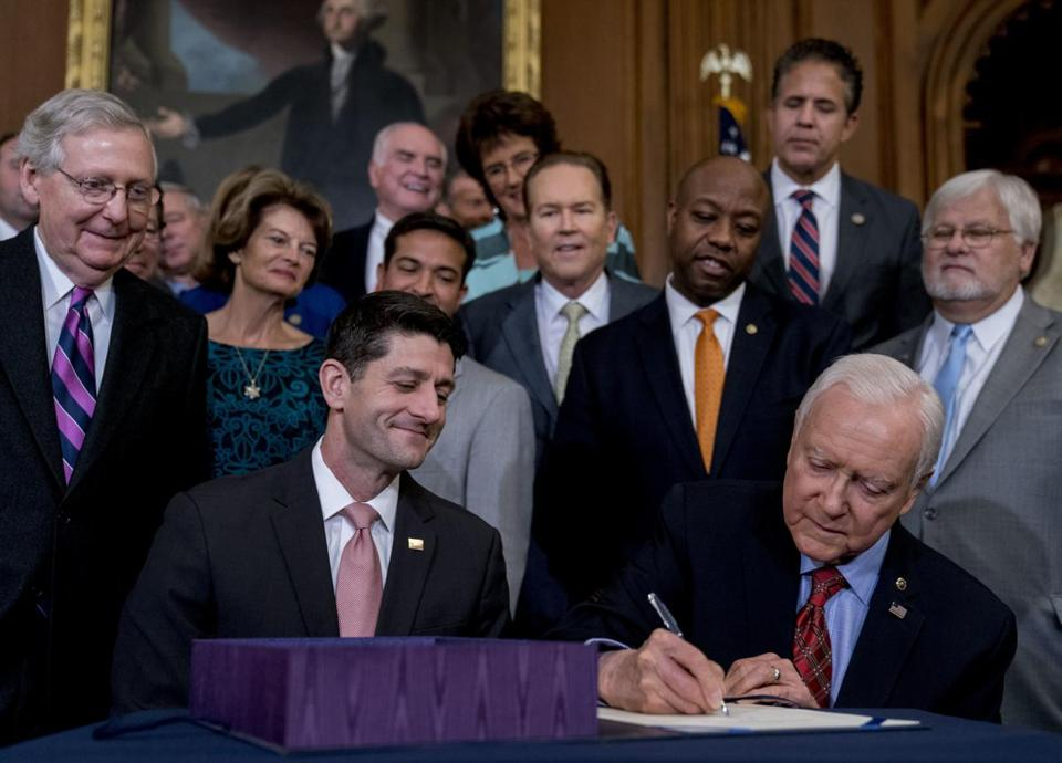 Senator Mitch McConnell (left), House Speaker Paul Ryan, and other lawmakers watched Senator Orrin Hatch sign the final version of the GOP tax bill.
