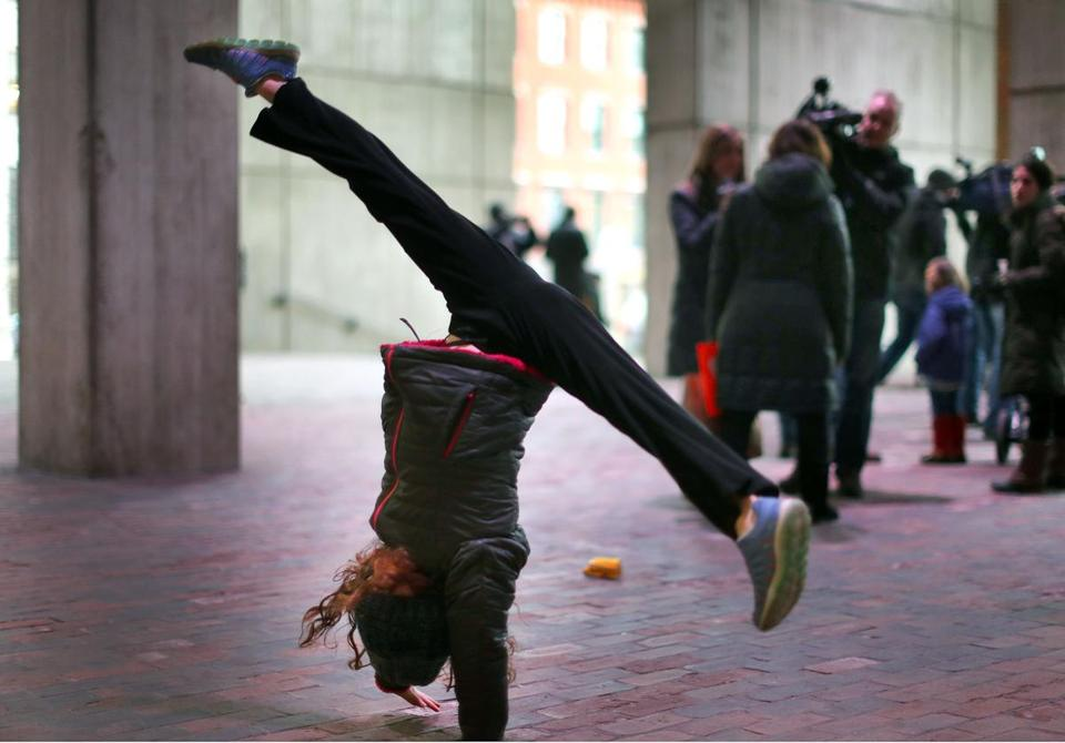 Boston-12/22/2017 A happy Beatrice Graf, 9, a third-grader at Mission Hill School does a somersault at a small showing of parents and students at City Hall. She was happy because her school start time will not change and she just found out about it when she arrived with her mother. Parents came to voice their concern about the start time of elementary schools in Boston. Even though superintendent Chang has decided not to implement the new start times, people still showed up to voice future concerns.John Tlumacki/Globe staff (metro)