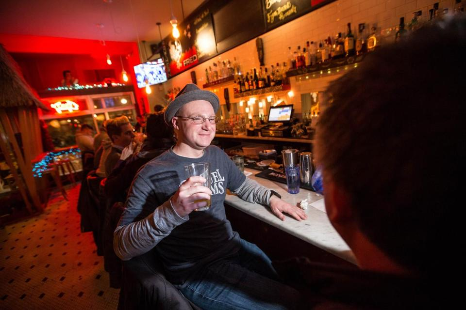 Shaun Dagle of Waltham sits at a crowded bar at Highland Fried.