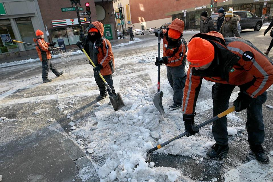 Workers for the Downtown Boston Business Improvement District cleared ice and snow from the intersection of Arch and Summer Streets.