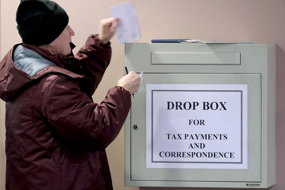 Residents filled out paper work and use locked drop boxes to pay their taxes at the Fairfax County Government Center  Thursday in Fairfax, Vir.