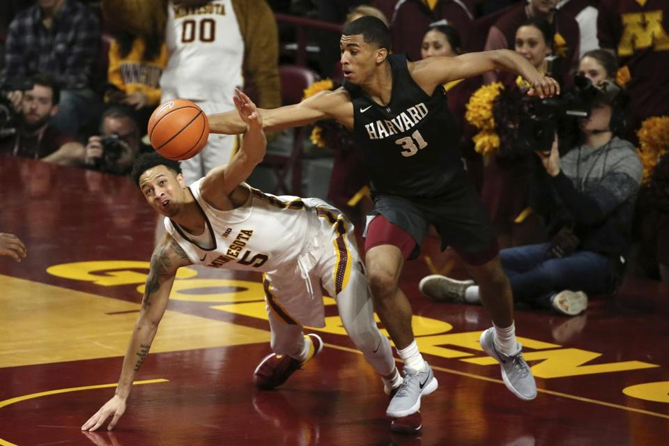 Minnesota guard Amir Coffey (5) and Harvard forward Seth Towns (31) fight for a loose ball in the second half of an NCAA college basketball game in Minneapolis on Saturday, Dec. 30, 2017. Minnesota won, 65-55. (Anthony Souffle/Star Tribune via AP)