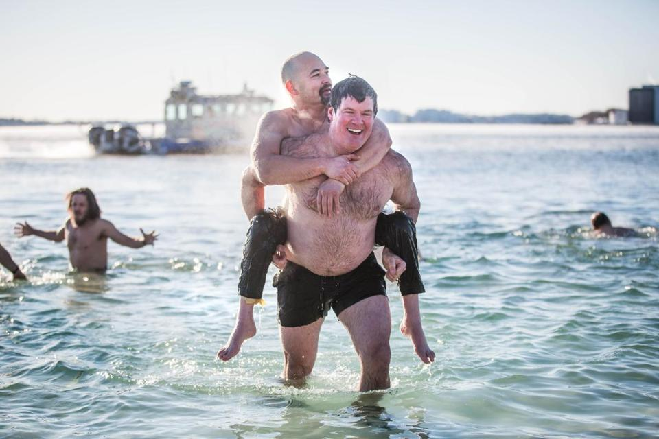 Steve Sheerin, right, carried Erik Kondo, who is disabled, Brownies New Year's Day Swim Monday.