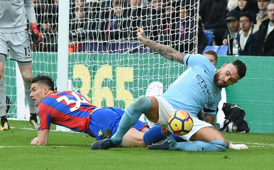 Manchester City's Nicolas Otamendi (right) battles Crystal Palace's Martin Kelly for the ball in London.