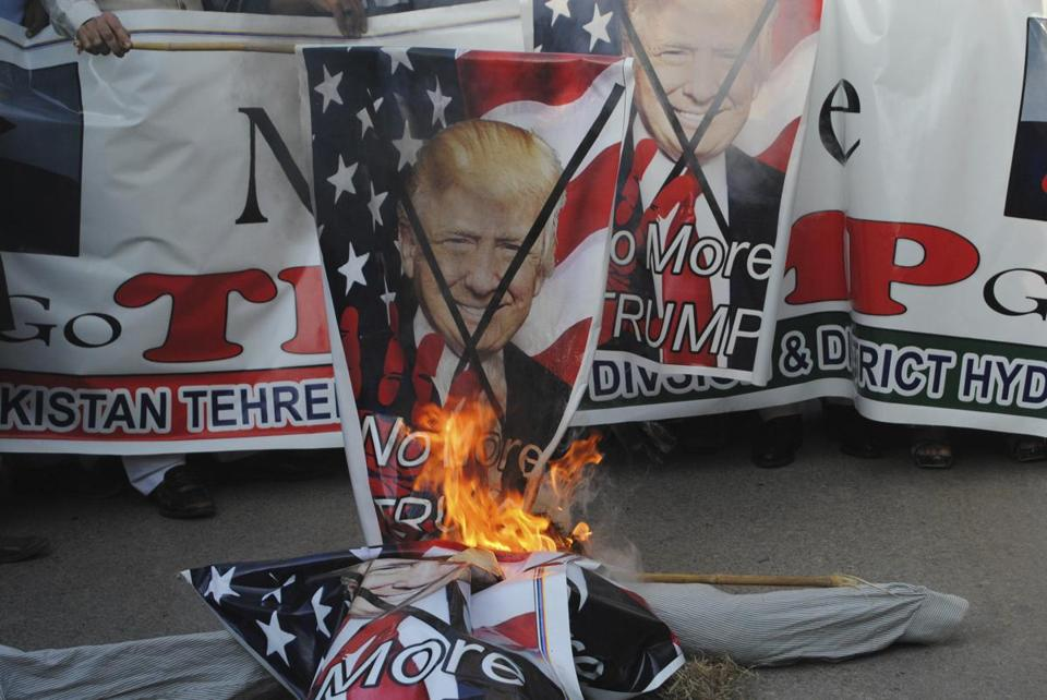 Pakistani protesters burned banners showing US President Donald Trump in Hyderabad, Pakistan, Tuesday.