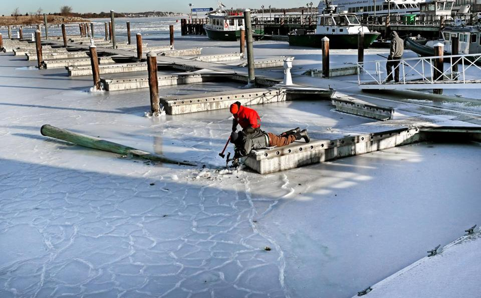 HINGHAM, MA - 1/02/2018: With an ax and pic L-R Tyler Borris (red ) and Willie Fessenden with Hingham Shipyard Marinas free up a finger dock and a piling that snapped off from the ice. (David L Ryan/Globe Staff ) SECTION: METRO TOPIC stand alone photos