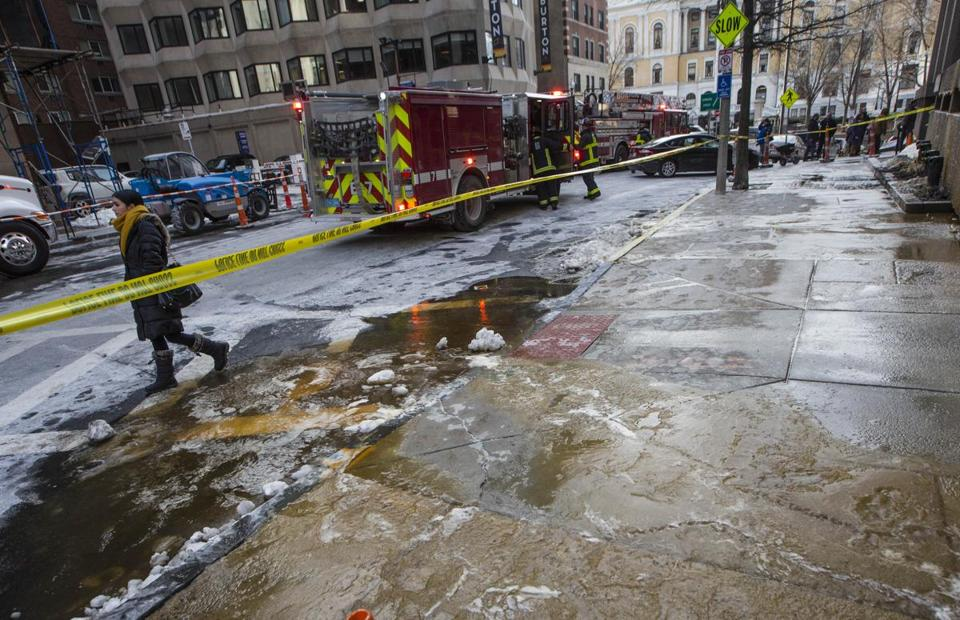 Sheets of ice caused by a water main break were taped off in front of the John McCormack Building in Boston on Wednesday.