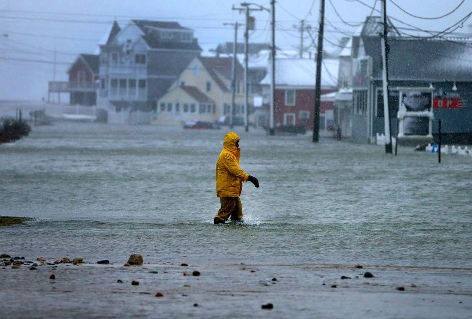 A man walked through a flooded section of Brant Rock after the afternoon high tide.