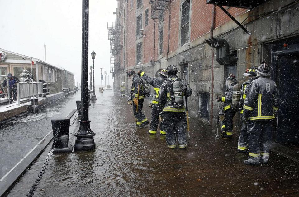 Boston firefighters worked at the scene of flooding from Boston Harbor on Long Wharf in Boston.
