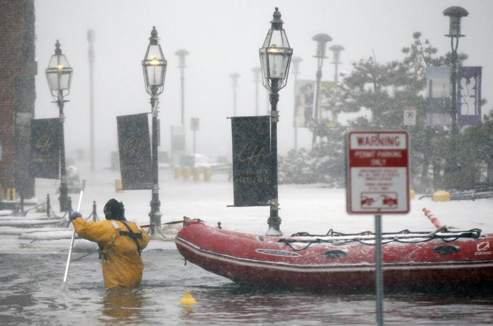 A Boston firefighter wades through flood waters from Boston Harbor on Long Wharf in Boston, Thursday, Jan. 4, 2018. A massive winter storm swept from the Carolinas to Maine on Thursday, dumping snow along the coast and bringing strong winds that will usher in possible record-breaking cold. (AP Photo/Michael Dwyer)