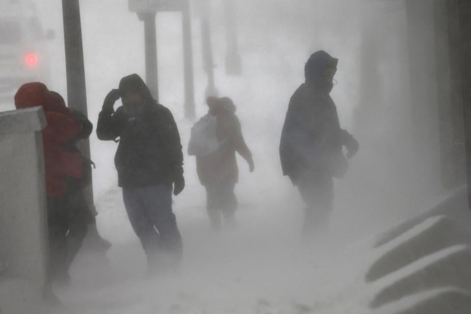 Pedestrians struggled in high winds and snow on Congress Street in downtown Boston.