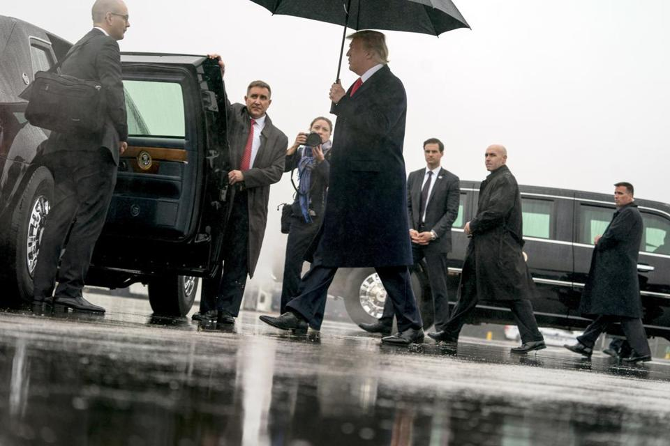 President Donald Trump walks in the rain as he arrives at Nashville International Airport in Nashville, Tenn., Monday, Jan. 8, 2018, to speak at the American Farm Bureau Federation's Annual Convention. (AP Photo/Andrew Harnik)