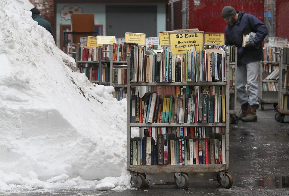 People browsed carts of books for sale on a sidewalk.