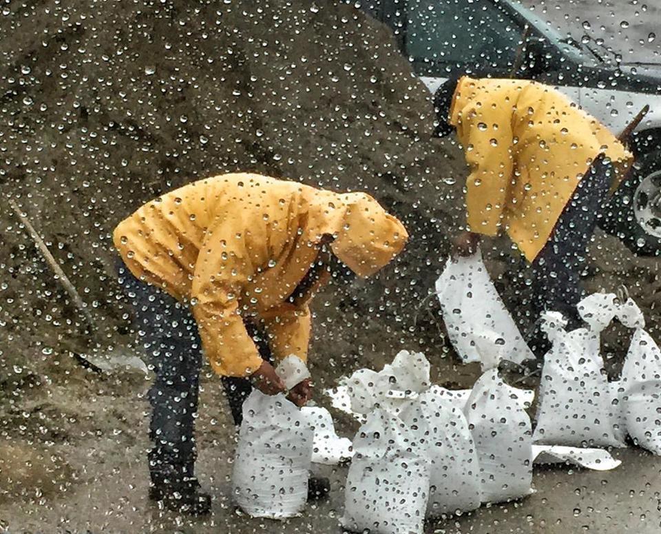 Sandbags are filled under the rain in Santa Barbara, California.