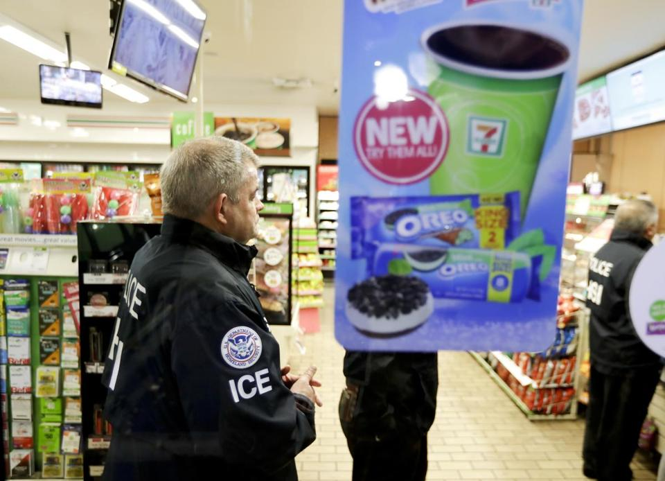 US Immigration and Customs Enforcement agents serve an employment audit notice at a 7-Eleven convenience store Wednesday in Los Angeles.