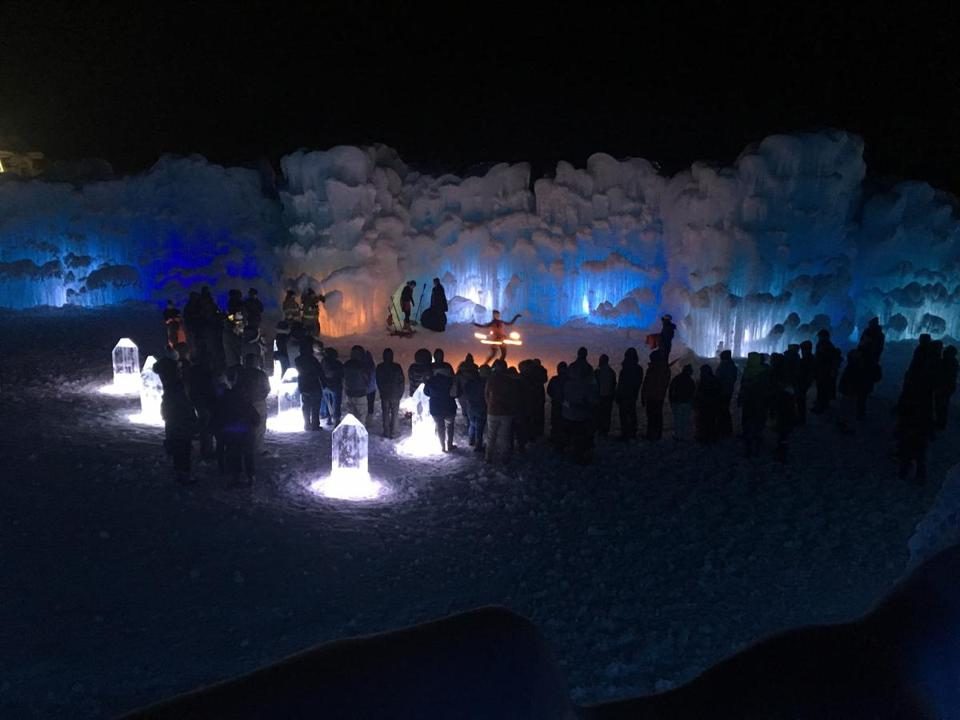 An outdoor fire performance amid ice and lights at Ice Castles.