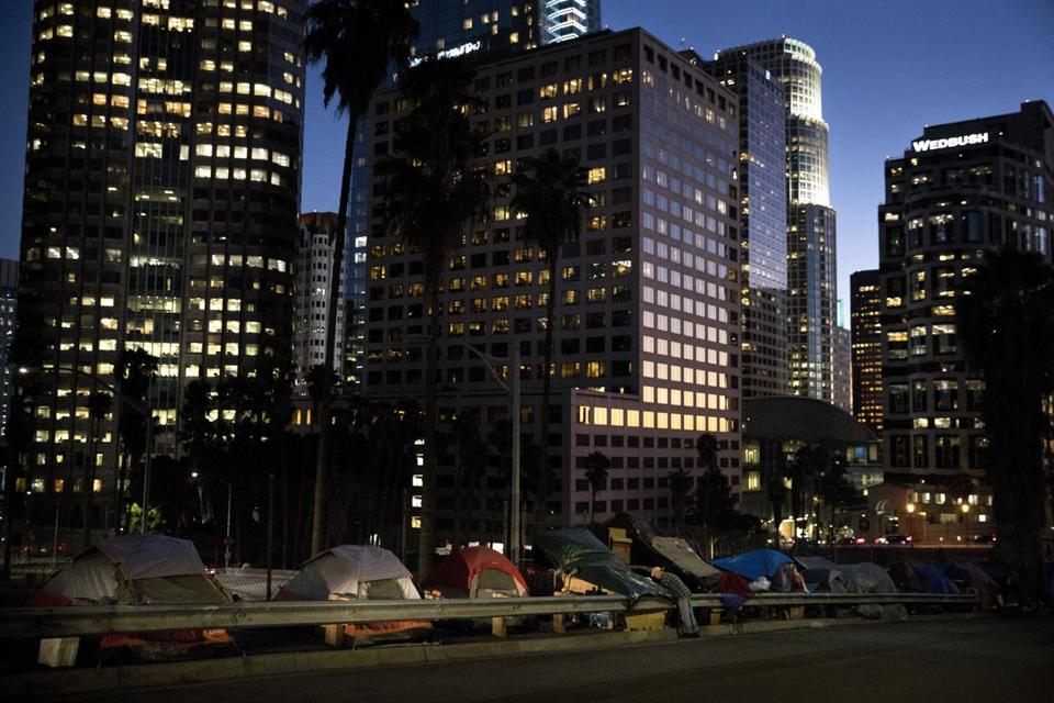 FILE - In this Dec. 1, 2017 file photo, homeless tents are dwarfed by skyscrapers as 63-year-old Vincent, who only gave his first name, sorts his belongings in Los Angeles. President Donald Trump's administration is announcing $2 billion in grants for local programs to deal with homelessness. The funding total is a record for the Continuum of Care grants, but only a small increase over recent years. The announcement comes as the administration is calling for cuts to housing programs and as the West Coast is dealing with a homeless crisis. (AP Photo/Jae C. Hong, File)