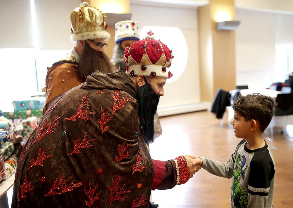 Tomas Gonzales, portraying one of the Three Kings, greeted Edrick Claudio at a Roxbury celebration Saturday.