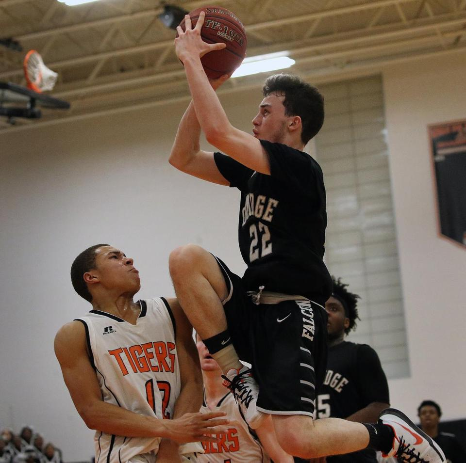 Newton North's Noah Neville (left) drew an offensive charge from Cambridge's Aidan Keefer.