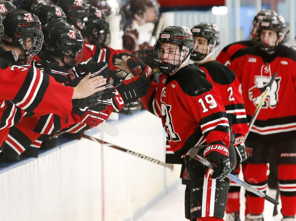 Reading's Michael Tobin (19) is congratulated by teammates after scoring the first of his two goals against Belmont during their hockey game in Belmont, Mass., Saturday, Jan. 13, 2018. (Winslow Townson for The Boston Globe)