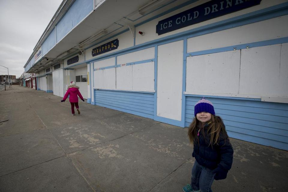 Anabella Reale (left), 6, and her sister, Cecilia, 4, played outside the buildings their parents recently bought opposite Nantasket Beach in Hull.