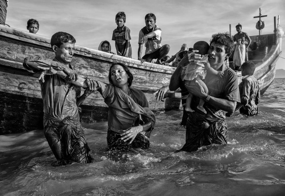 COX'S BAZAR, BANGLADESH - OCTOBER 01: (One of a 115-image Best of Year 2017 set) A Rohingya refugee woman is helped from a boat as she arrives exhausted on the Bangladesh side of the Naf River at Shah Porir Dwip after fleeing her village in Myanmar, on October 1, 2017 in Cox's Bazar, Bangladesh.
