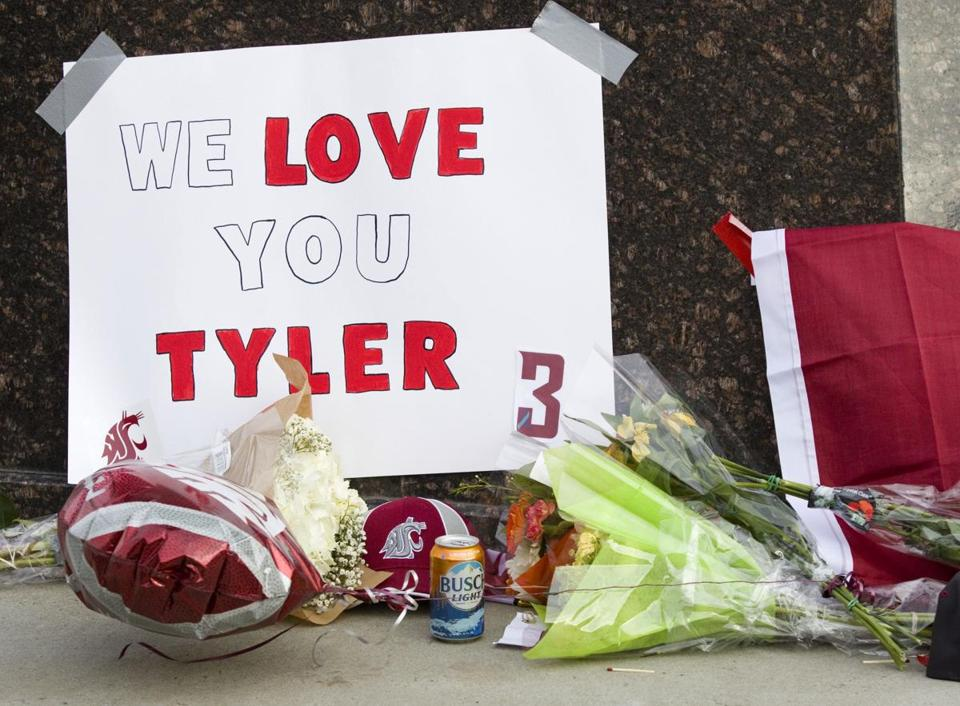 Items were left at a makeshift memorial for Washington State quarterback Tyler Hilinski outside Martin Stadium in Pullman, Wash., Wednesday.