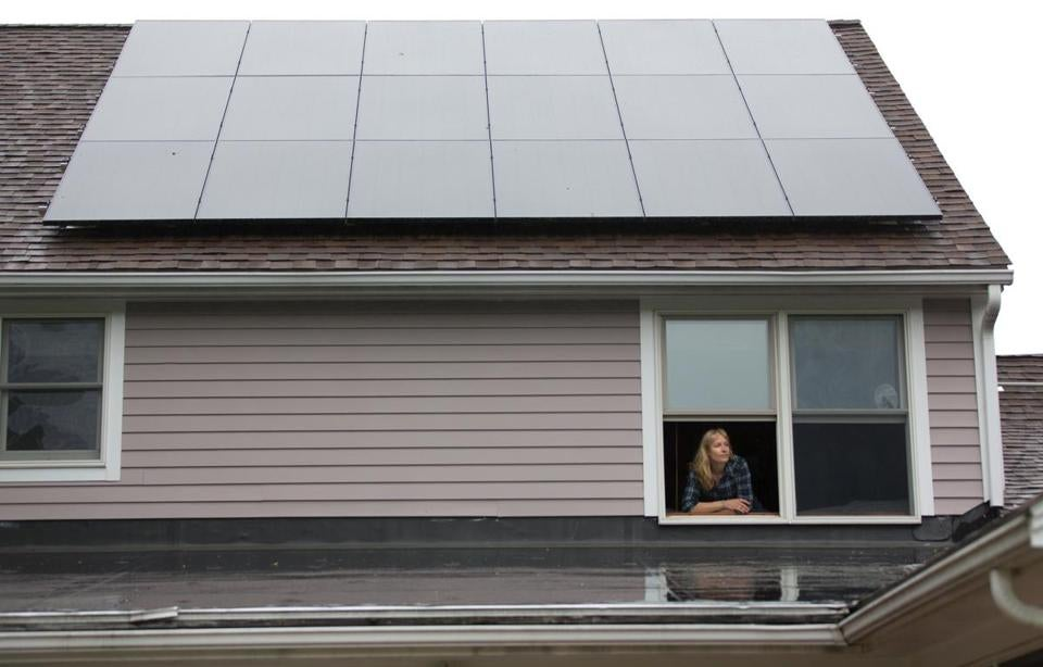 The solar industry says systems like those at Irene Kneeland's Sutton home should not face new fees.