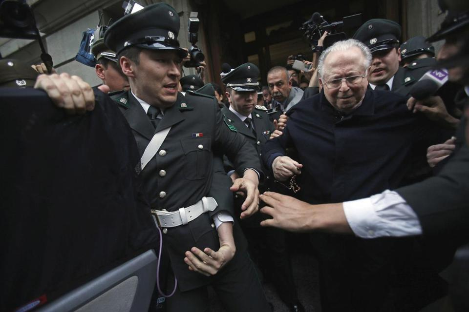 Fernando Karadima is escorted from a court, after testifying in a case that three of his victims brought against the country's Catholic Church in Santiago, Chile in 2015.