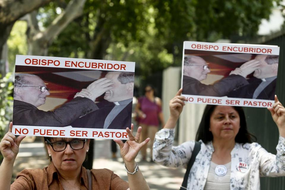 "Members of the movement Laicos de Osorno held up images showing the Rev. Fernando Karadima, and his protege Juan Barros, bishop of Osorno, with a message that reads in Spanish: ""A bishop who covers up cannot be a priest,"" during a demonstration in front of the Apostolic Nunciature, in Santiago, Chile last week."