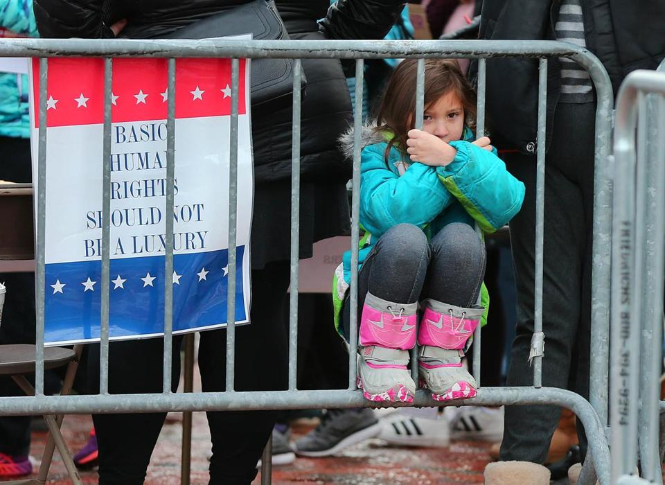 Sorayah Melendez, 7, from Dedham peered through a fence during a women's march and rally held on the Cambridge Common on Saturday.