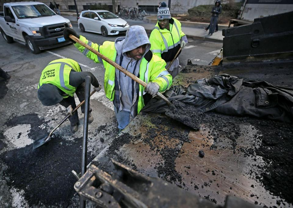 Stacey Harris (center) removed fill from a truck bed and a crew worked on St. James Avenue.