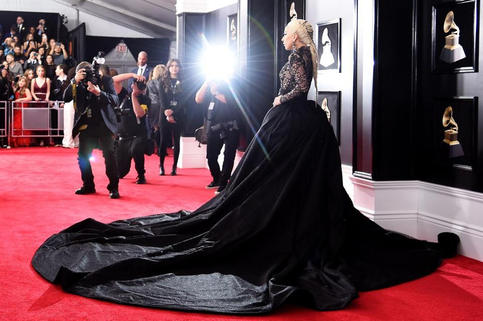 Gaga was in a black lace top and leggings with a full skirt and train, white rose in place and her hair swept into a fishtail braid with black lacing. Her signature towering platform shoes — black boots this time around— were on her feet.