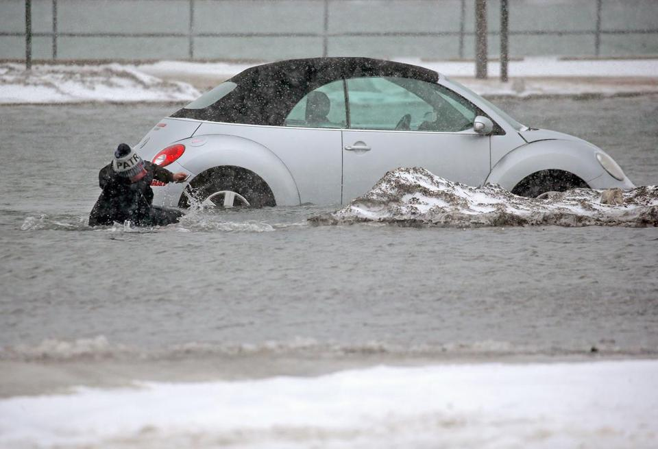 Beth Troupe tripped after she tried to move her car in a flooded parking lot in Scituate on Tuesday.