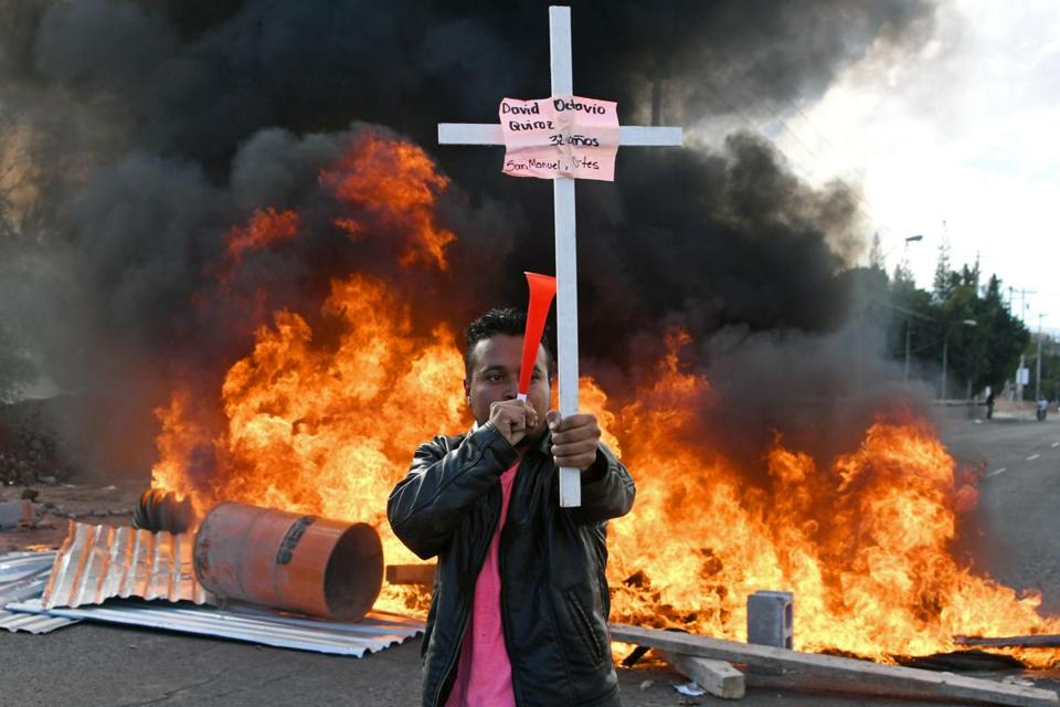 A supporter of the Honduran Opposition Alliance Against the Dictatorship held a cross among barricades protesting the reelection of President Juan Orlando Hernández.