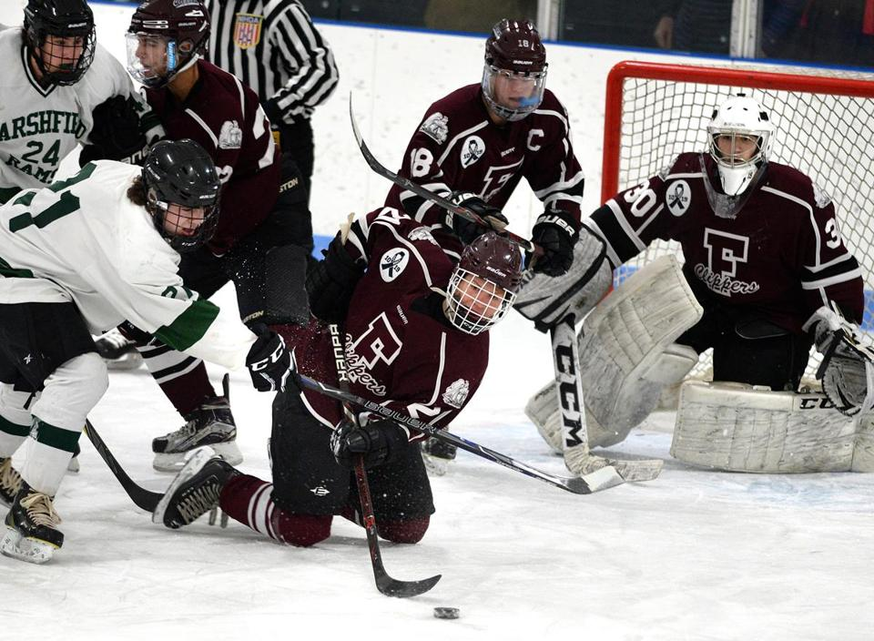 Pembroke 01/31/2018: Falmouth's #21, Matt Haley moves the puck from his knees infront of the net against Marshfield's #21, Cole McKenzie in the first period. Photo by Debee Tlumacki for the Boston Globe (sports)
