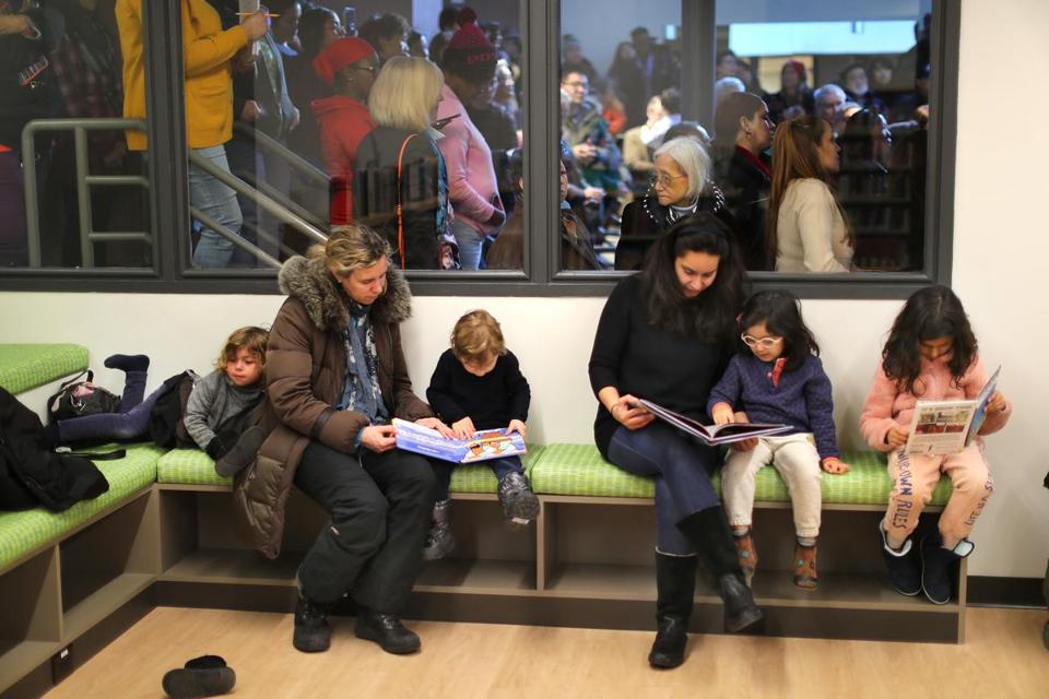 With the opening ceremony going on behind them, children and their parents remained engrossed in books at the new Boston Public Library branch in Chinatown.
