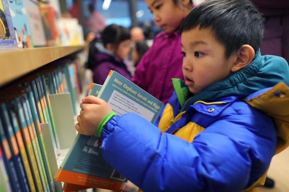 Michael Ruan, 5, looked at books at the new Boston Public Library temporary branch inside the China Trade Center.