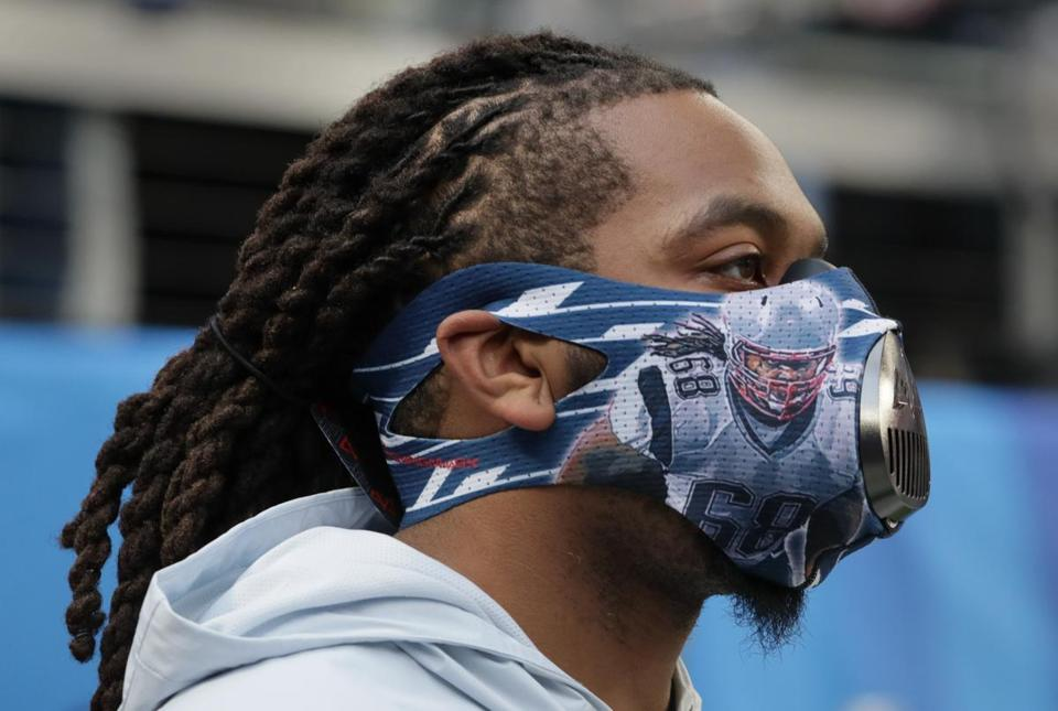 Patriots offensive lineman LaAdrian Waddle wears a training mask on the field during warmups.