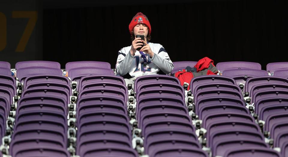 An early arriving Patriots fan records the scene, alone in a sea of purple seats.
