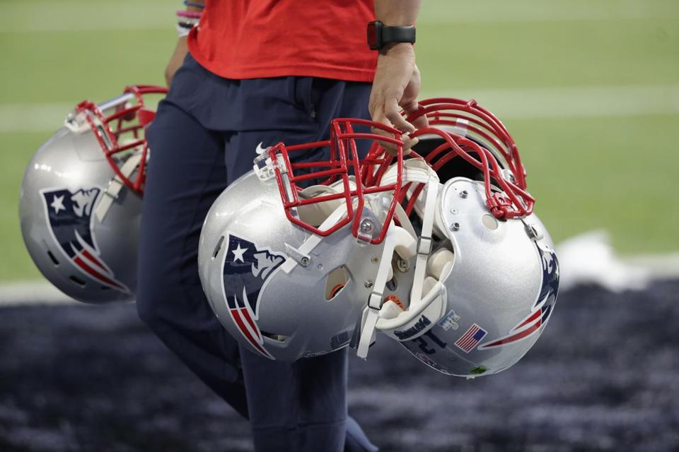 A handful of Patriots helmets are brought to the field.