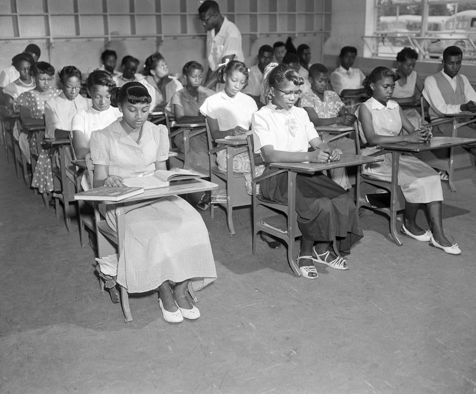 "Henrietta Hilton, front left, daughter of tenant farmer William Hilton, and her fellow students, are seen in their ninth grade classroom in Summerton, S.C., June 4, 1954. The classroom is in a newly built brick building that adjoins to the old wooden structure, which is the center of a controversy which led to one of four cases involving ""separate but equal"" facilities for blacks and whites. Others are not identified. (AP Photo/Rudolph Faircloth)"