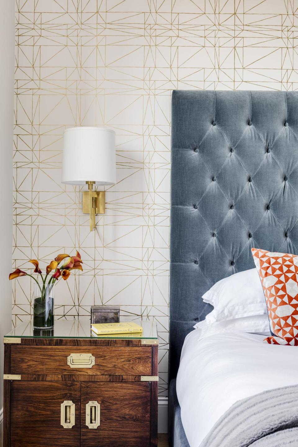 The tufted headboard of the Restoration Hardware platform bed is upholstered in slate blue velvet. Caroline chose the gold metallic geometric patterned Hygge & West wallpaper. The vintage John Stuart campaign-style nightstand is one of a pair Andrew already owned, bought online from InCollect.