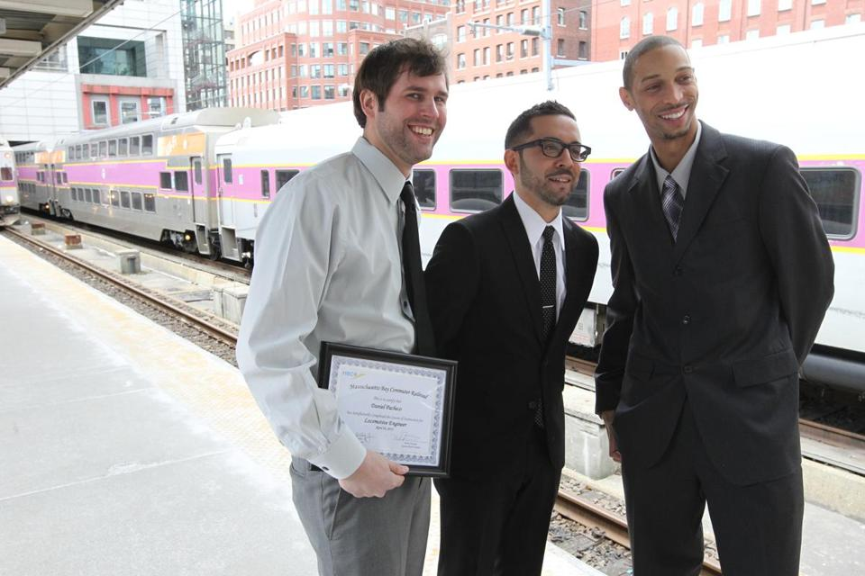 In 2013, Roberto Ronquillo III (middle) was honored with a certificate as a train service engineer at Boston's South Station.