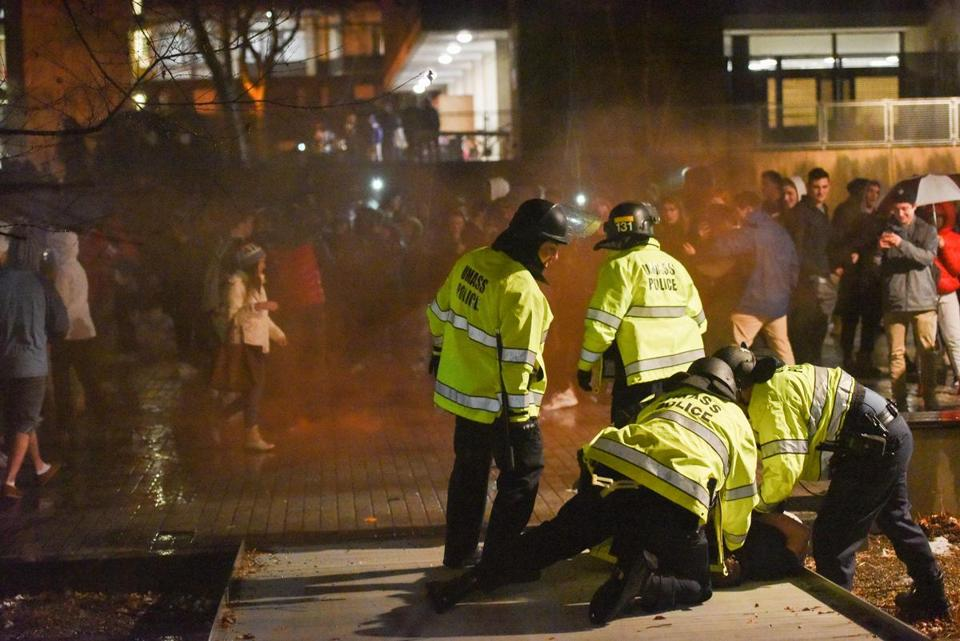Two UMass Amherst police officers deploy tear gas on UMass Amherst students and people rallying and rioting in the Southwest living area of the UMass Amherst campus on Sunday.