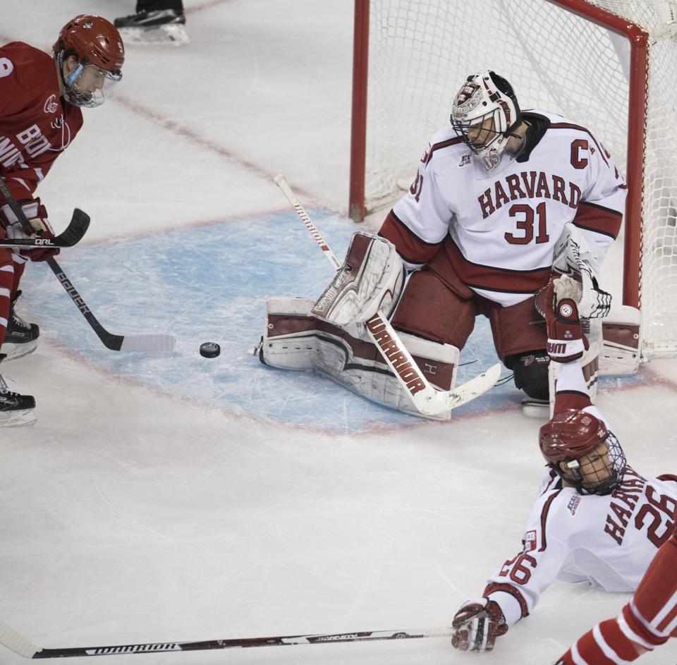 Harvard goalie Merrick Madsen makes a pad save in the second period, as BU's Logan Cockerill looks for the rebound.