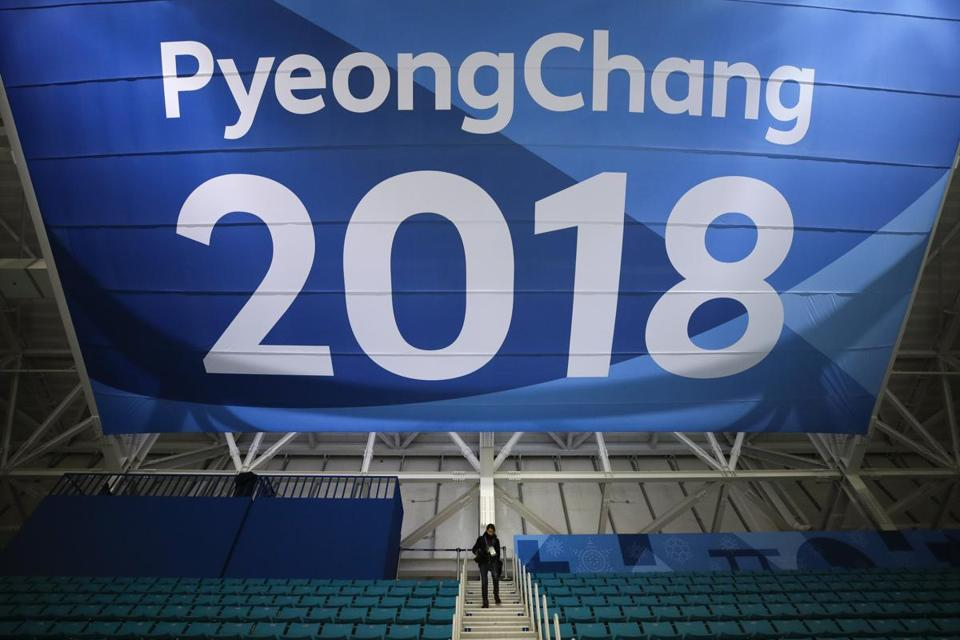 FILE - In this Feb. 6, 2018 file photo, a photographer walks down the steps underneath a large banner at the Gangneung Hockey Center ahead of the 2018 Winter Olympics in Gangneung, South Korea. Fresh off the Super Bowl, NBC begins more than two weeks of Winter Olympics coverage on Thursday, Feb. 8, with a new host, some new wrinkles and the hope that its business model keeps pace with the different ways people experience events on television and online. (AP Photo/, File)