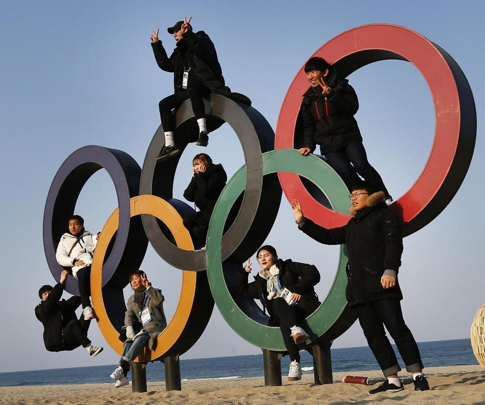 A group of people posed on the Olympic rings in PyeongChang, South Korea on Thursday.