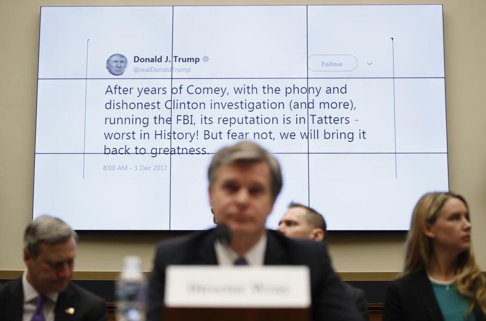 A tweet by President Donald Trump is displayed behind FBI Director Christopher Wray as he testifies during a House Judiciary hearing on Capitol Hill in Washington, Thursday, Dec. 7, 2017, on oversight of the Federal Bureau of Investigation. (AP Photo/Carolyn Kaster)